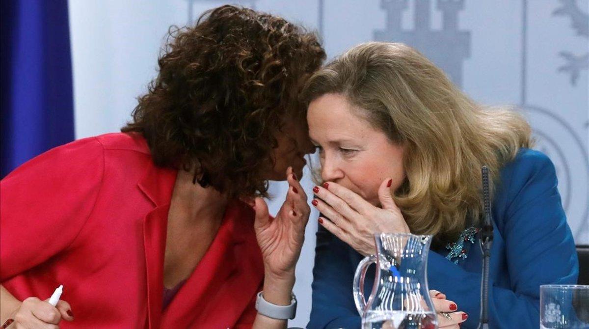 La ministra de Hacienda, María Jesús Montero, y la vicepresidenta económica, Nadia Calviño, conversan al oído tras el Consejo de Ministros del 11 de febrero.