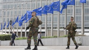 Soldados belgas patrullan junto a las banderas de la UE que ondean a media asta por el atentado de Manchester, el 23 de mayo, en Bruselas.