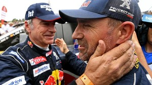 Stéphane Peterhansel, 'monsieur Dakar', ganador de 13 rallys Dakar, felicita a su amigo y compañero en Peugeot, Carlos Sainz.