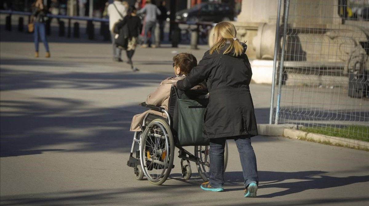 Una cuidadora acompaña a una mujer en silla de ruedas en Barcelona.