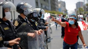 Una mujer, frente a los policías apostados en el Congreso, en Lima, este domingo.