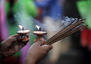Una mujer nepalí hindú prende incienso al rezar una oración para una vida larga y llena de amor.