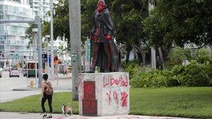 Una mujer pasa por una estatua de Juan Ponce en Miami, este jueves.