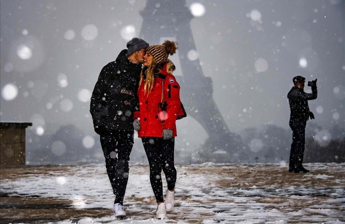 Una pareja se hace carantoñas bajo la mirada dela Torre Eiffel, mientras la nieve cae sobre París.