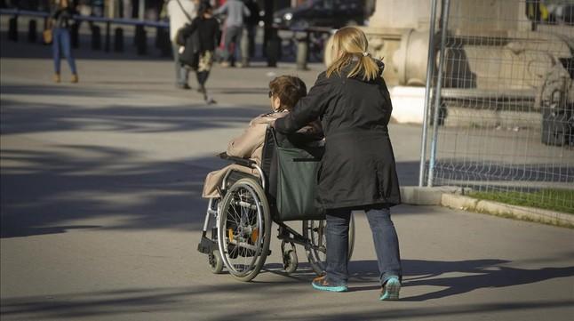 Una persona en silla de ruedas, acompañada de una cuidadora, en Barcelona.