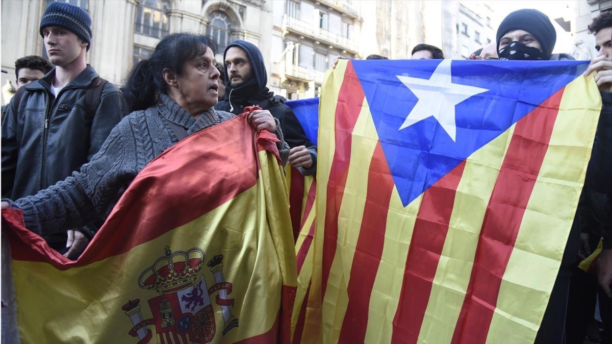Una señora muestra la bandera española ante una joven con el rostro tapado que exhibe una estelada.