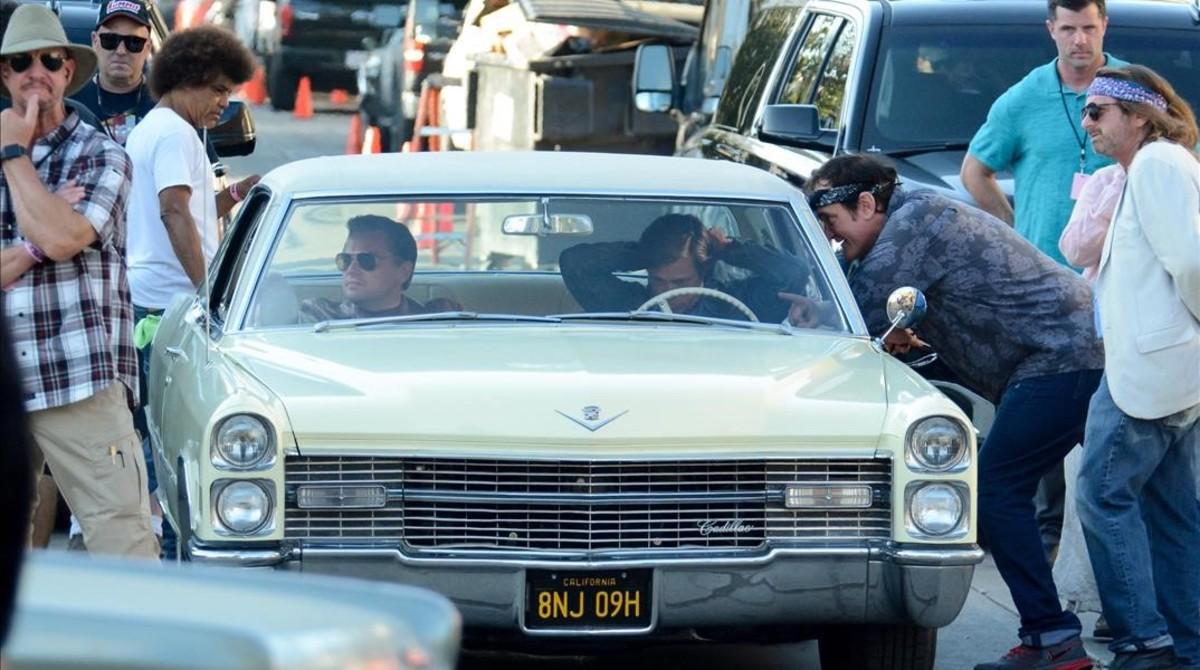 Tarantino se asoma a la ventanilla del conductor para das instrucciones a Brad Pitt (al volante) y Leonardo DiCaprio, en el rodaje de Once upon a time in Hollywood.