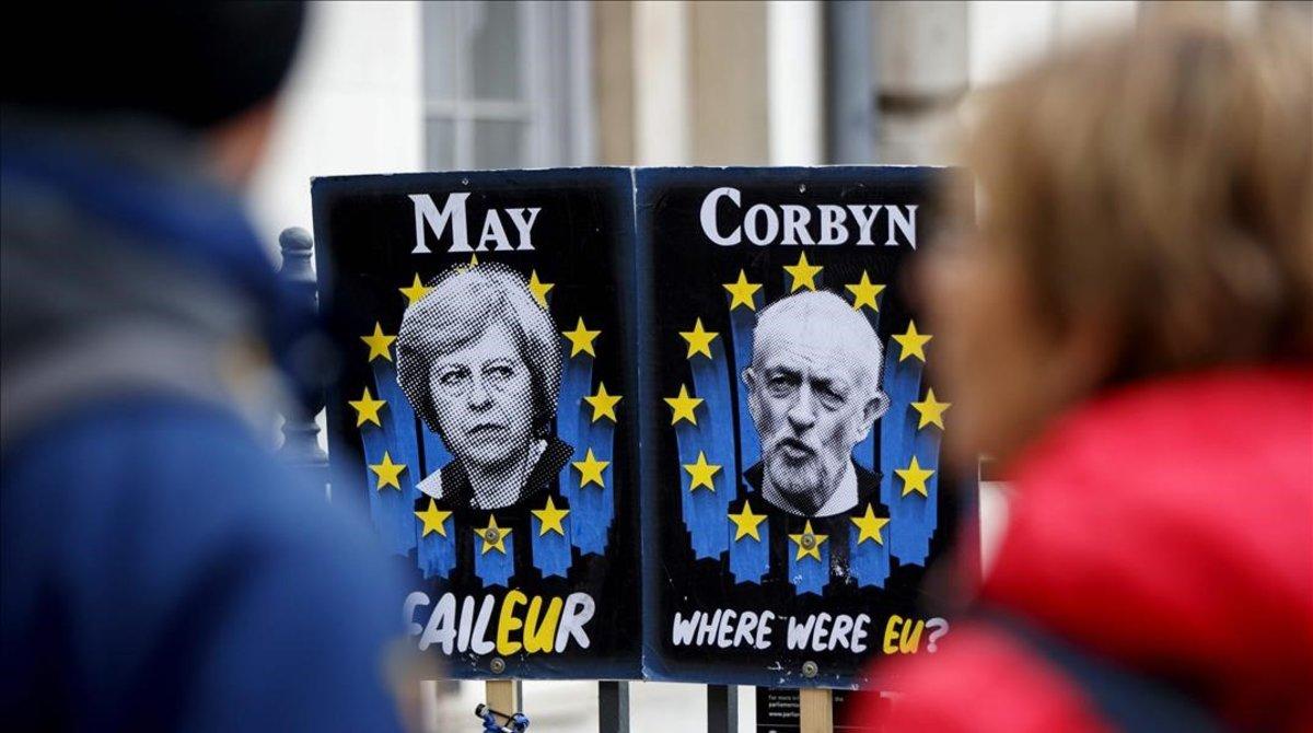 Unos peatones pasan junto a carteles con la primera ministra británica, Theresa May, y el líder del Partido Laborista, Jeremy Corbyn, cerca del Parlamento, en Londres.