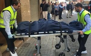 Unos sanitarios retiran un cadáver de la casa donde se produjo el doble crimen, en Premià de Mar.