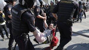 Varios policías detienen a una mujer durante la manifestación de este sábado en el centro de Moscú.