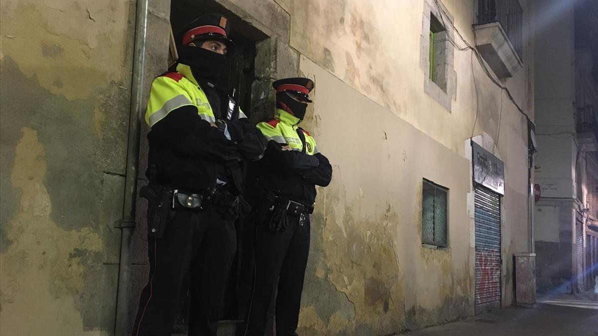 Dos mossos ante el portal de la calle de la Riera Alta donde se ha cometido el crimen.