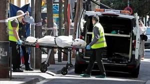 Miembros de los servicios funerarios trasportan el cadaver de la mujer asesinada en un comercio deSabadell, la semana pasada.