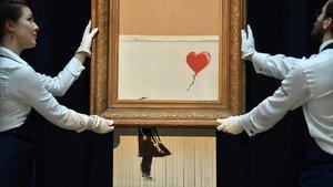 Empleados de Sothebys muestranLove is in the bin' de Banksy, la nueva pieza resultado de la autodestrucción, en plena subasta, de Girl with a balloon.
