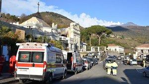 Ambulancias y vehículos de rescatecerca de la iglesia muy dañada de Maria Santissima mientras penachos de humo salen del volcán Etna en Fleri