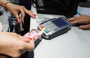 Un cliente realizando un pago con un tarjeta en un comercio.