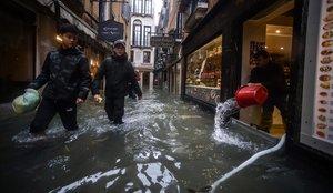 Un comerciante achica agua de su tienda, en el centro de Venecia.