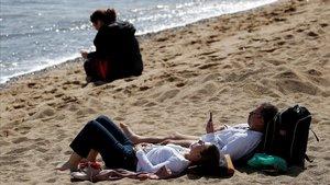 Varias personas toman en sol en la playa en Barcelona el pasado fin de semana.