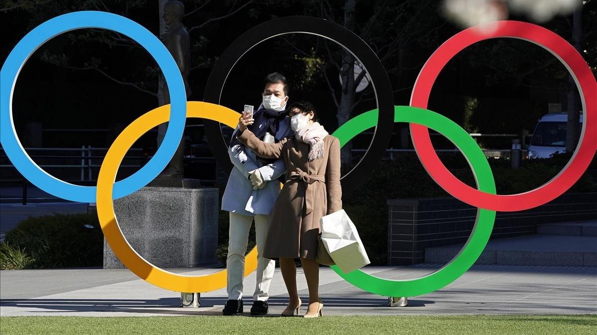 Una pareja ante el monumento de los Anillos Olímpicos, frente a la sede del Comité Olímpico de Japón.