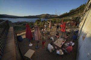 Familiaresy amigos se reúnen en la terraza de un restaurante en el pantano de El Burguillo (Ávila).