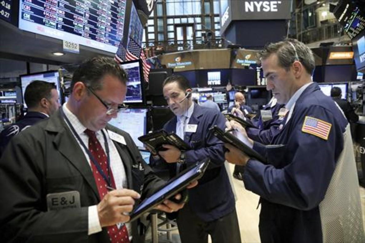 Agentes de bolsa en Wall Street, atentos ayer a la evolución de los mercados.