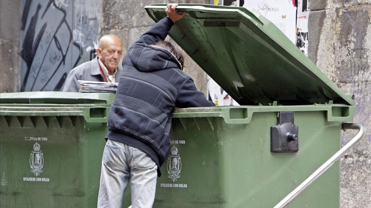 Un mendigo busca entre la basura de un contenedor, en Pontevedra. / MARTA G. BREA