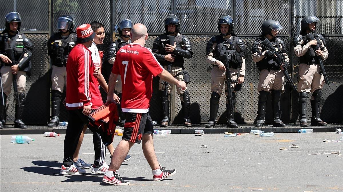 Aficionados del River pasan por delante de las fuerzas policiales tras la suspensión del partido el pasado sábado.