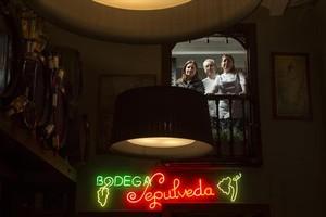 Desde el balcón y sobre el emblemático rótulo luminoso, Núria, Josep y Sònia Solà.