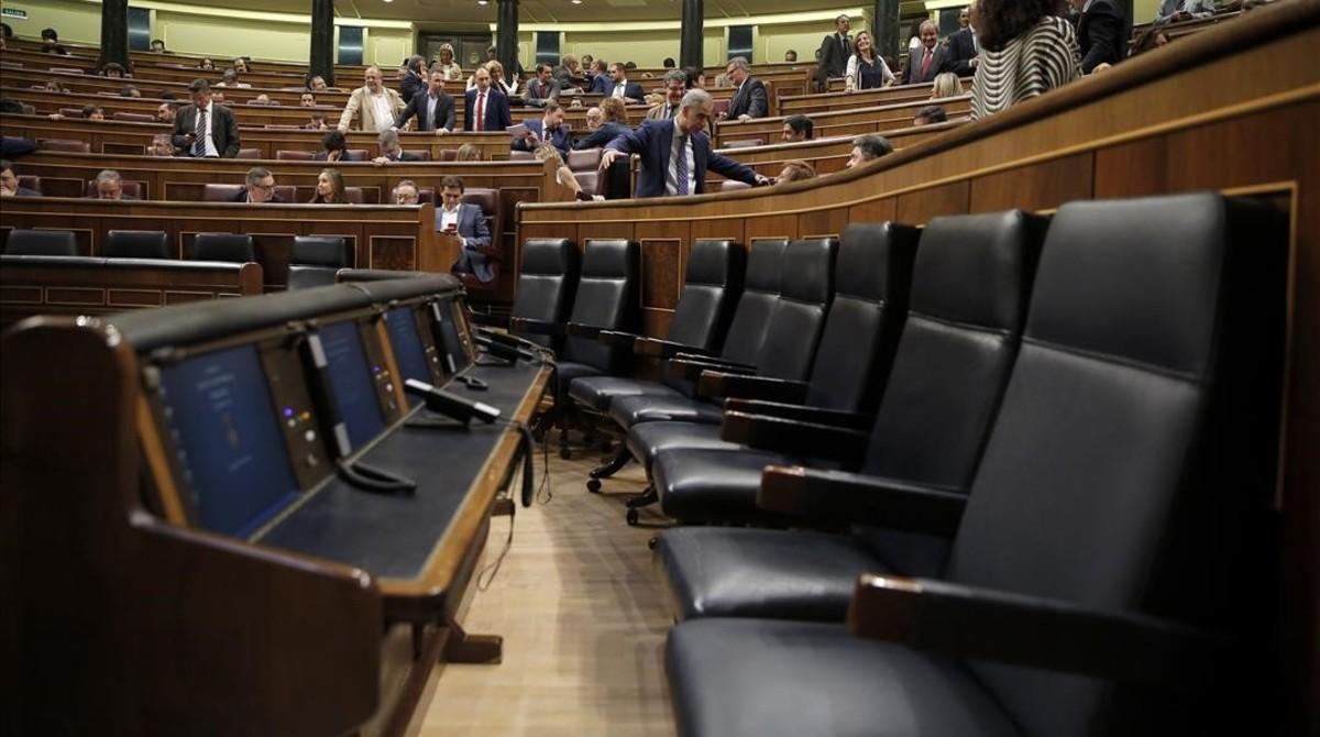 La bancada azul del Gobierno permanece vacía mientras la oposición pide explicaciones al también ausente Luis de Guindos, en el pleno del Congreso.