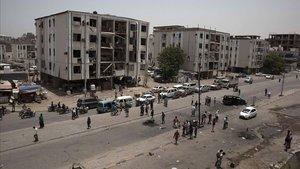 Civiles y fuerzas de seguridad permanecen a las afueras de la comisaría de policía atacada, este jueves, en el centro de Adén.