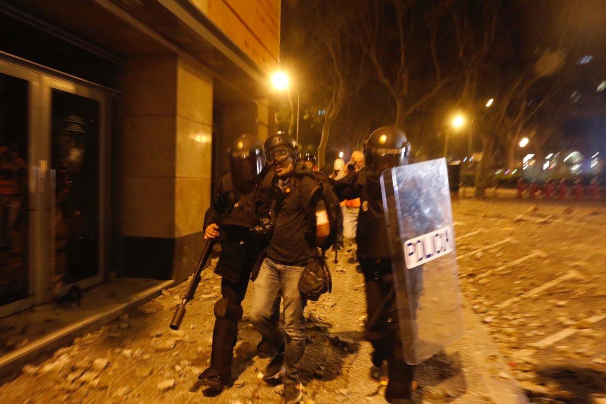 Dos agentes se llevan detenido al fotógrafo de El País.