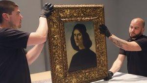 Dos personas sostienen el cuadro de Botticelli 'Retrato de Michele Marullo Tarcaniota'.
