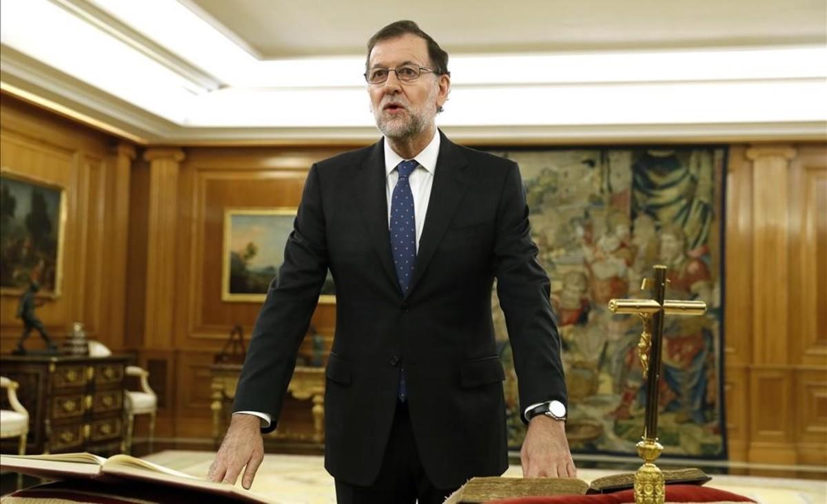 Mariano Rajoy jura el cargo de presidente del Gobierno ante la Biblia, la Constitución y un crucifijo, el 31 de octubre en la Zarzuela.