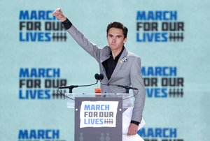 FILE PHOTO David Hogg a student at the Marjory Stoneman Douglas High School site of a February mass shooting which left 17 people dead in Parkland Florida thrusts his fist in the air as he speaks during the March for Our Lives event demanding gun control after recent school shootings at a rally in Washington U S March 24 2018 REUTERS Aaron P Bernstein File Photo