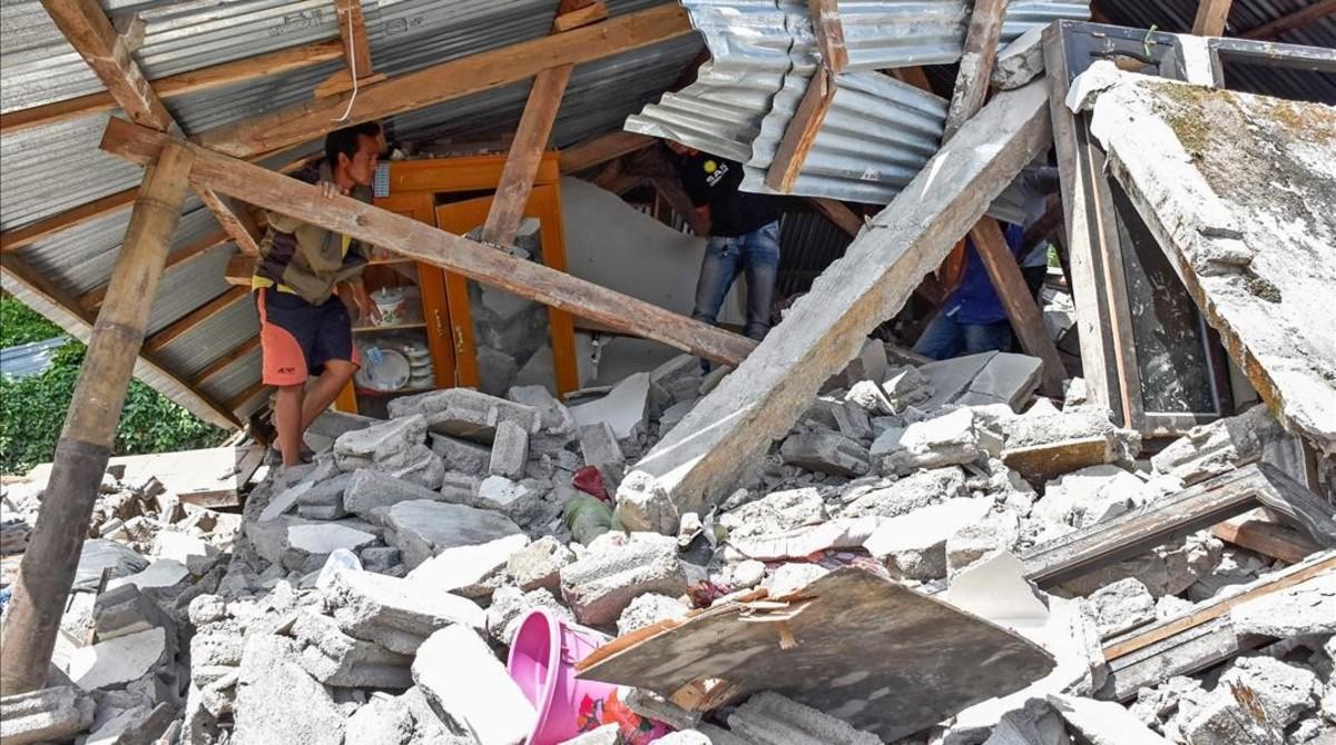 Un hombre comprueba el estado ruinoso de su hogar tras el terremoto que ha sacudido la isla indonesia de Lombok.