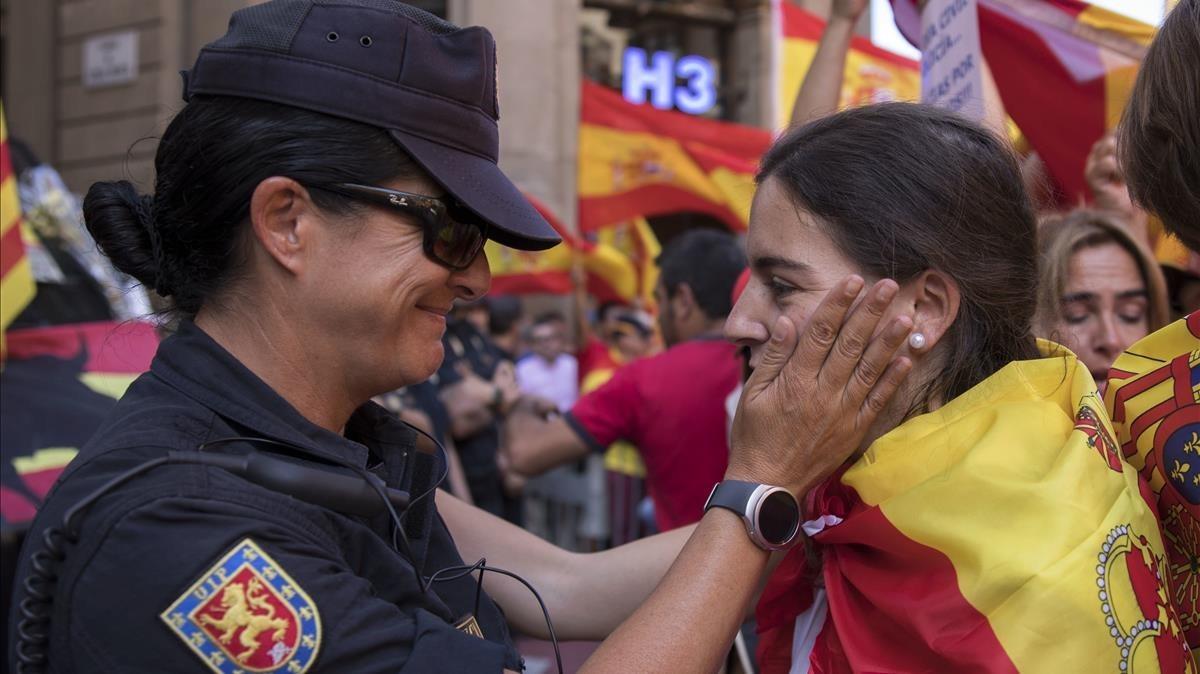 Un oficial de policía español habla con un manifestante