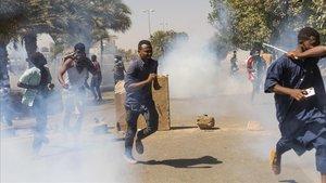 Manifestantes se protegen de los gases lacrimógenos de las fuerzas de seguridad en Jartum.
