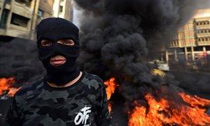Un manifestante quema neumáticos durante una protesta contra la corrupción y para reclamar más servicios básicos, en la plaza de Wathba, en Bagdad, el 1 de diciembre.