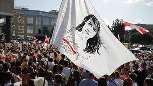 Manifestantes portan una bandera con un retrato de la líder opositora bielorrusa Svetlana Tikhonóvskaya, este lunes en Minsk.