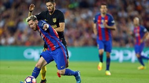 Messi disputa un balón con Carrasco en el Camp Nou antes de lesionarse.