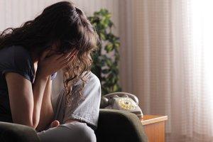 Mujer llorando en el sofá.