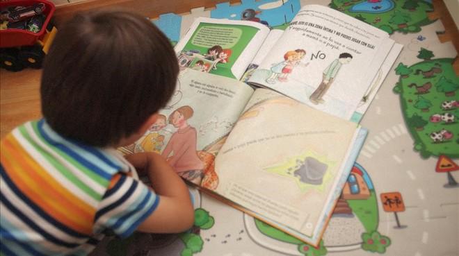 Un niño de tres años mira las viñetas de varios cuentos infantiles.