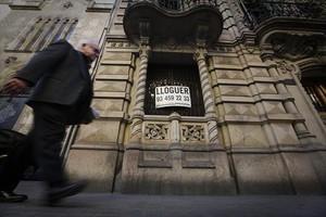 Un portal de la calle de València, con un cartel de piso en alquiler.