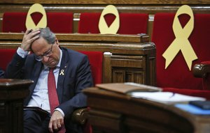 Catalan regional President Quim Torra puts his hand on his head during a parliamentary session, in Barcelona, Spain, Wednesday, Oct. 3, 2018. Torra issued an ultimatum to Spanish Prime Minister Pedro Sanchez on Tuesday over the wealthy northeastern regions future but it was promptly rejected by the Spanish government. Yellow ribbons on the seats are in support of Catalonian politicians who have been jailed on charges of sedition. (AP Photo/Manu Fernandez)