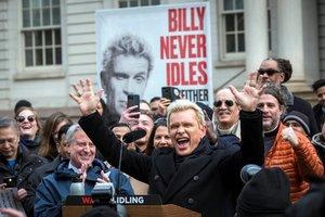 AME8772. NUEVA YORK (ESTADOS UNIDOS), 27/02/2020.- Fotografía cedida por el Ayuntamiento de Nueva York donde aparece la estrella del rock Billy Idol (d) mientras celebra junto al alcalde de la ciudad, Bill de Blasio (i-atrás), durante la presentación de una campaña medioambiental este jueves, en Nueva York (EE.UU.). Billy Idol participó este jueves en la presentación de una campaña medioambiental en Nueva York que pretende reducir el número de vehículos que, pese a no estar en marcha, permanecen con el motor encendido y por lo tanto contaminan de manera innecesaria. La iniciativa, titulada Billy nunca está inactivo, y tú tampoco deberías (Billy Never Idles, Neither Should You), está impulsada por el Ayuntamiento de Nueva York, y pide a los neoyorquinos que informen de los conductores que no apagan el motor cuando están detenidos. EFE/ Michael Appleton/ Ayuntamiento de Nueva York SOLO USO EDITORIAL/NO VENTAS