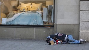 Un hombre duerme frente a un escaparate en el centro de Barcelona.