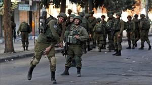 Un soldado israelí lanza un petardo contra un grupo de palestinos en Hebron durante un enfrentamiento, el pasado 13 de octubre.