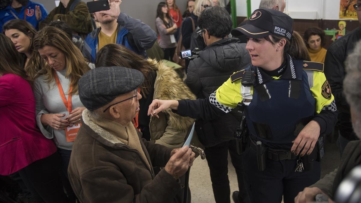 Una agente de laGuardia Urbana orientando a una persona de edad avanzada en el colegio Ausias March de Les Corts.