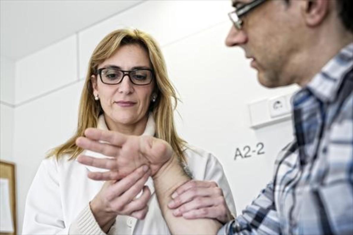Una doctora especialista en traumatología comprueba la funcionalidad de la mano de un paciente.