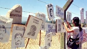 Una mujer cuelga carteles de chilenos desaparecidos en la cerca de Colonia Dignidad, que sirvió de centro de tortura de Pinochet.