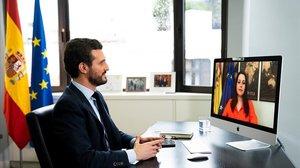 Pablo Casado, en su despacho de la sede del PP, en Génova, e Inés Arrimadas, en su casa, durante la videoconferencia de este viernes.